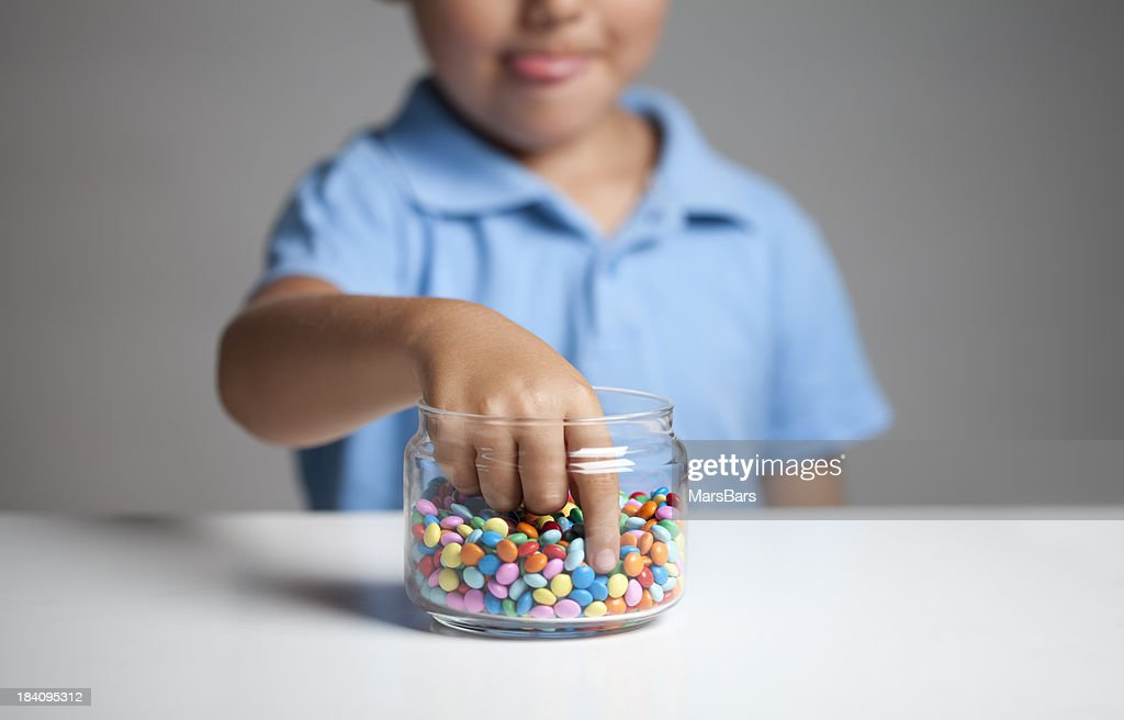 Little boy taking candy from jar : Stock Photo