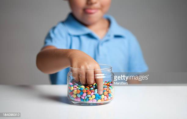 Little boy taking candy from jar