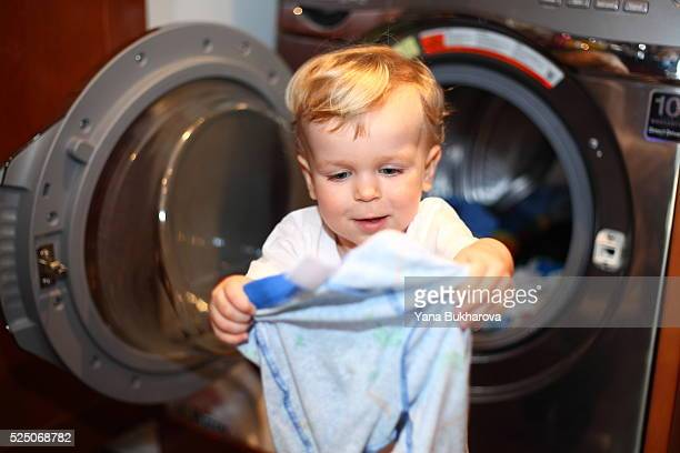 Little boy taking clothes out of the washing machine