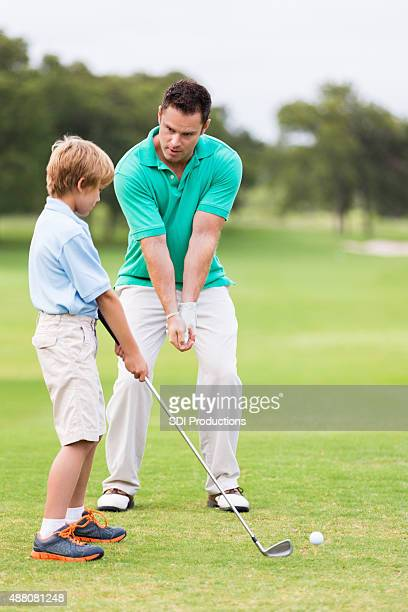 Little boy taking golf lessons from pro instructor