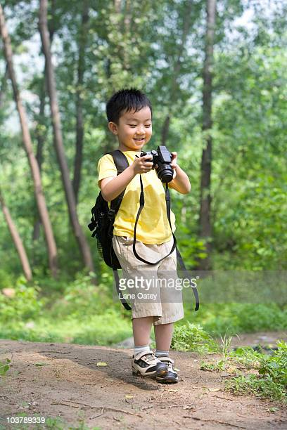 Little boy taking photos in nature