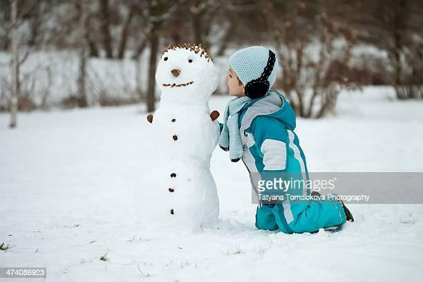 Little boy, talking with a snowman, having fun