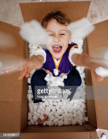 Little boy throwing packing peanuts : Stock Photo