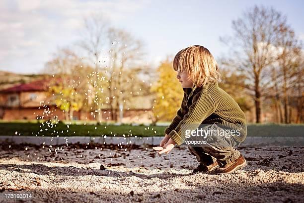 Kleine Junge werfen sand entfernt