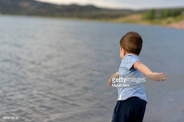 Little boy throwing stones at the lake