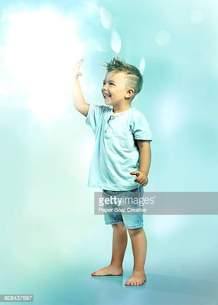 Little boy touching floating ball of light