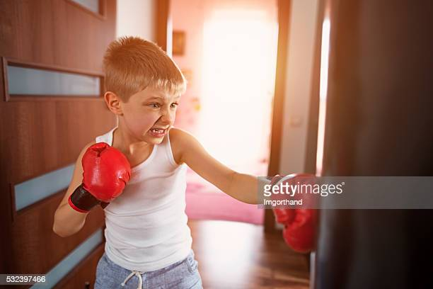 Little boy training with punching bag at home