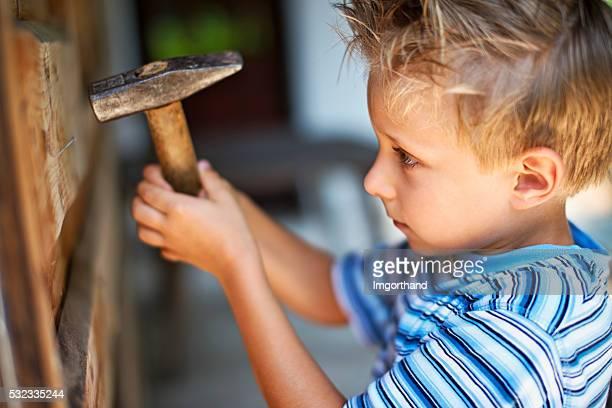 Petit garçon essaie de marteau de manucure et pédicure