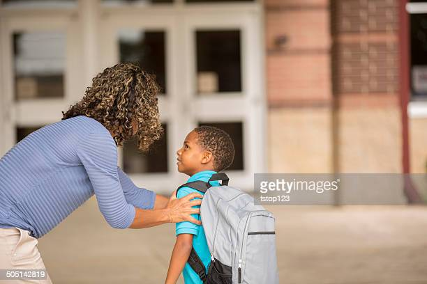 Little boy unsure on his first day of school.  Mother.
