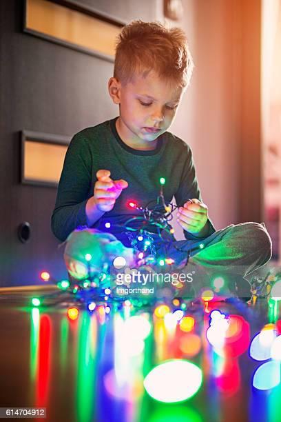 Little boy untangling christmas lights