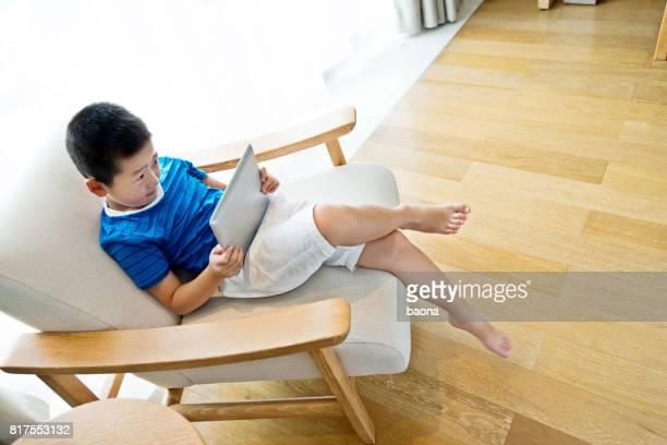Little boy using a digital tablet in armchair