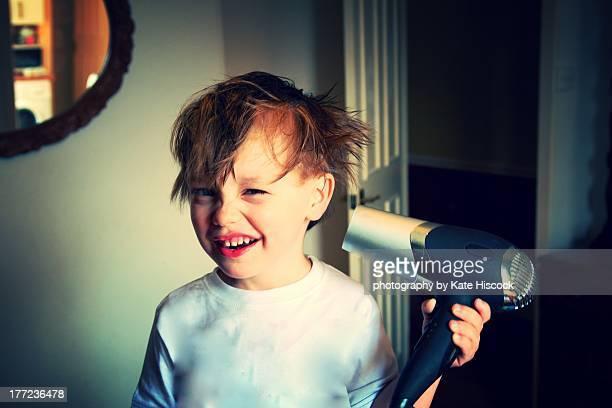 Little boy using a hair dryer