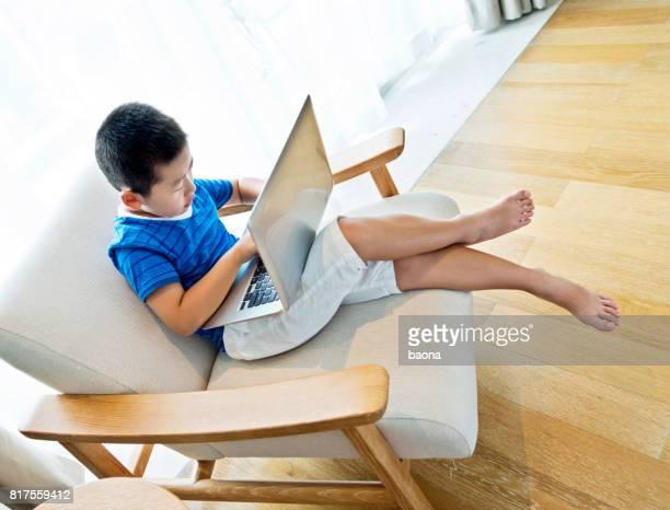 Little boy using a laptop in armchair