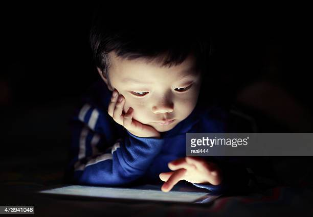 Little boy using digital tablet in bed