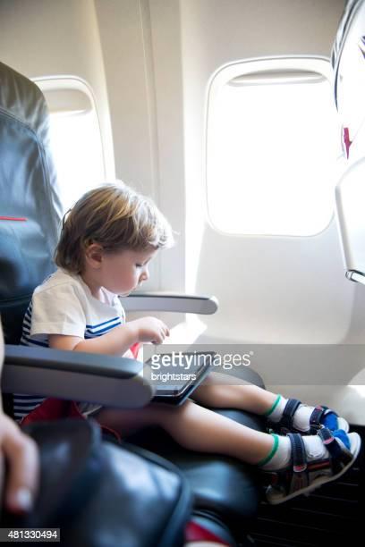 Petit garçon à l'aide de tablette numérique sur l'avion