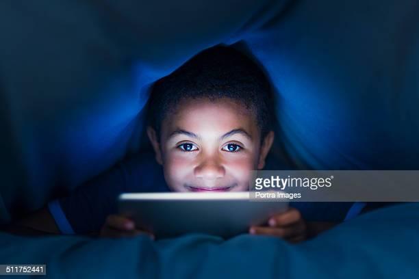 Little boy using digital tablet under blanket