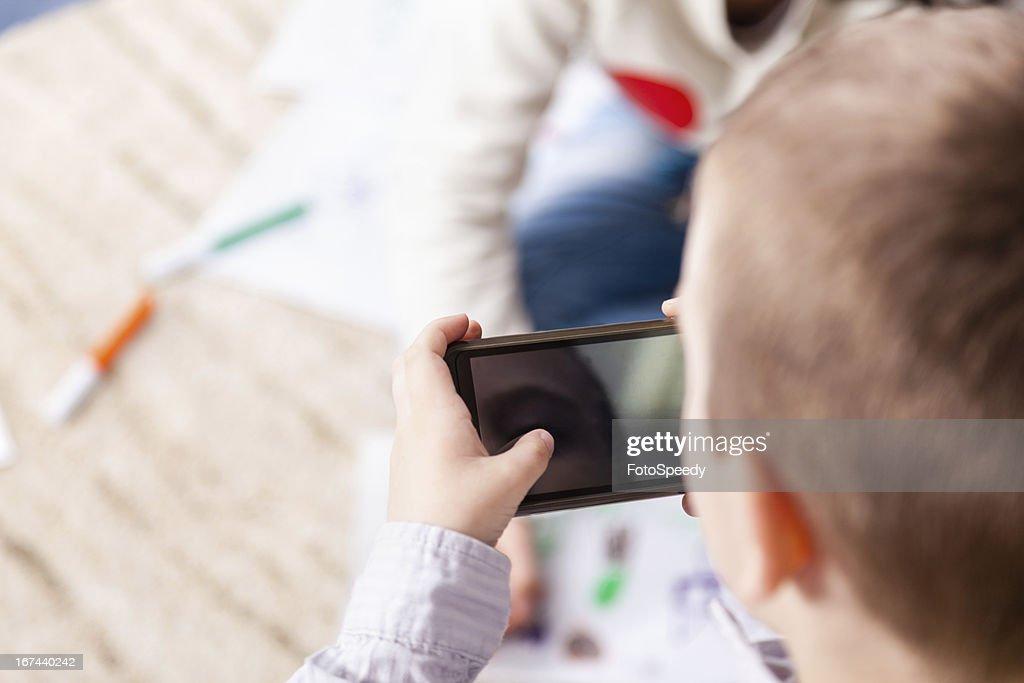 Little boy using smartphone : Stock Photo