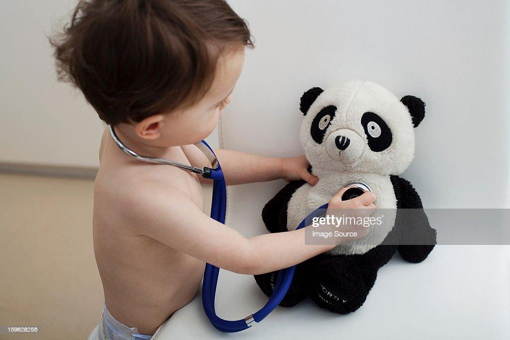 Little boy using stethoscope on panda toy : Stock Photo