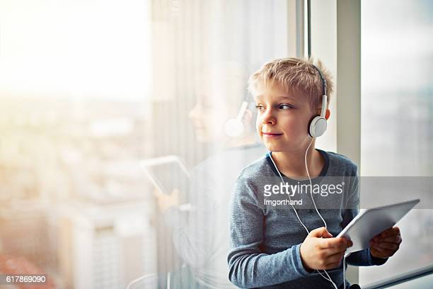 Little boy using tablet with headphones