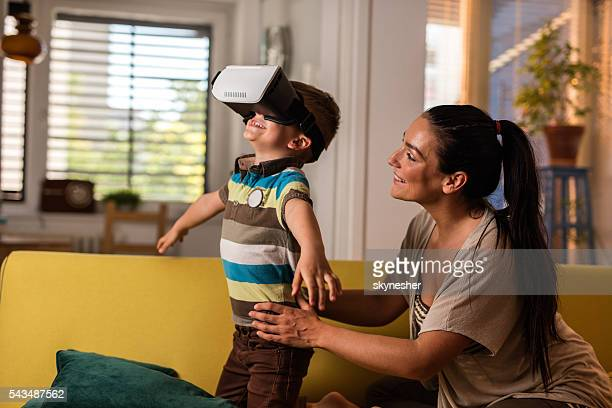 Little boy using virtual reality simulator with his mother.