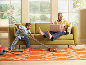 Little Boy Vacuuming Beneath his Father's Feet