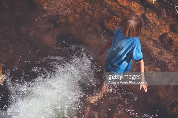 Little boy walking in creek.