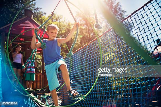 Little boy walking in modern ropes course playground