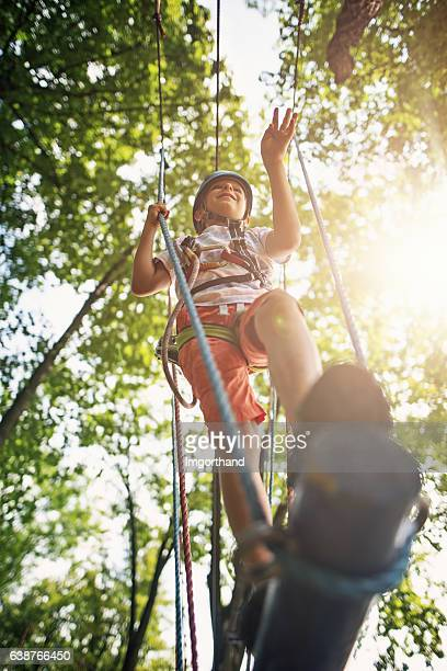 Little boy walking in ropes course in outdoors adventure park