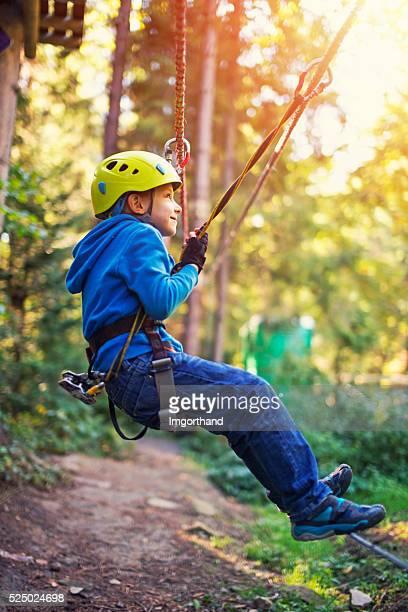 """Petit garçon marchant sur la ligne de parc d """" aventures en plein air"""