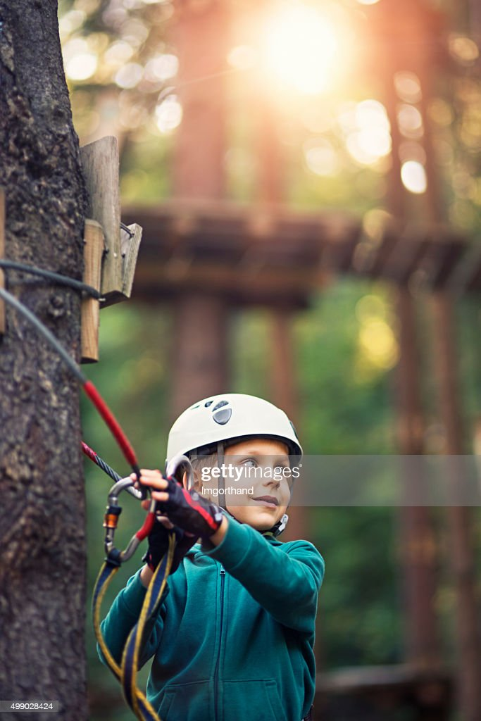 Little boy walking on ropes course in outdoors adventure park