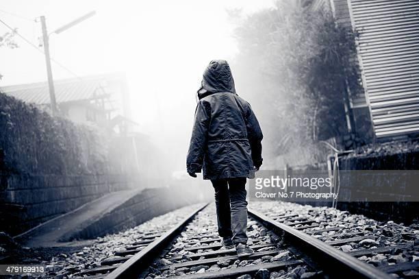 Little boy walking on train tracks