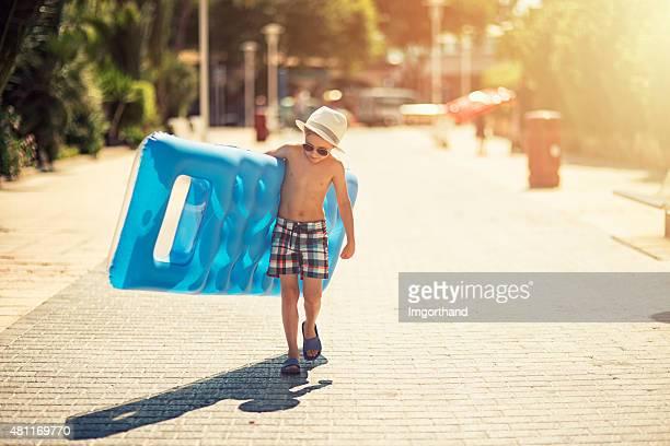 Bambino a piedi alla spiaggia con un letto