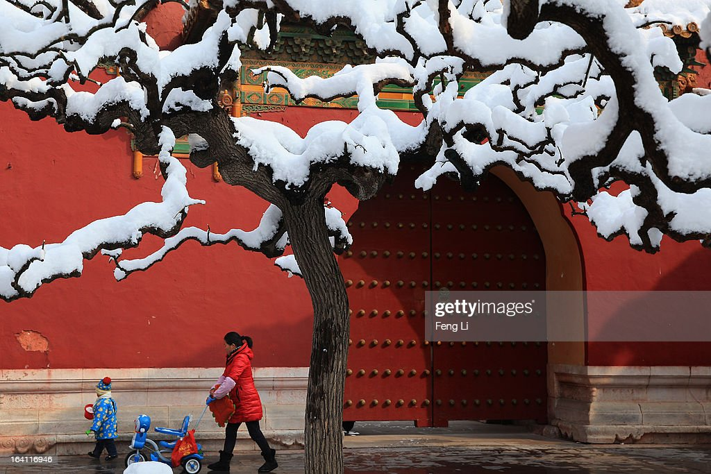 A little boy walks with his mother at the Imperial Ancestral Temple following overnight snowfall on March 20, 2013 in Beijing, China. Beijing witnessed a heavy spring snowfall with a depth reaching 10-17 centimeters overnight.