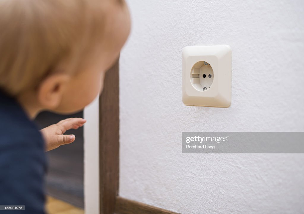 Little boy (1 y) wants to touch power outlet : Stock Photo