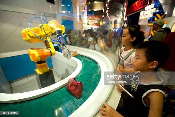 A little boy watches a robot pick up little bags in Shanghai's Science and Technology Museum on August 5 2010 in Shanghai China