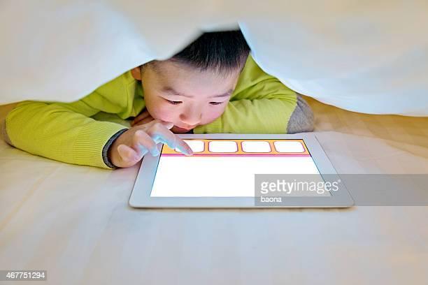 Kleiner Junge beobachten digitalen tablet im Bett