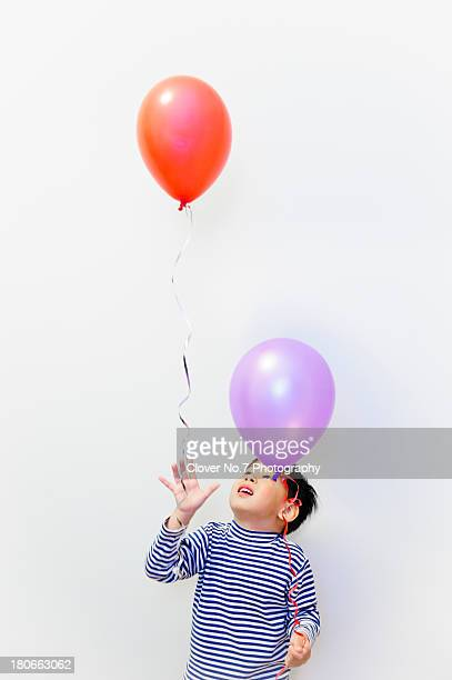 Little boy watching the balloons fly