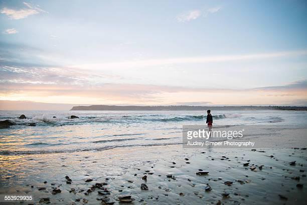 Little boy watching waves on beach