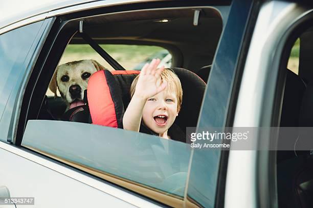 Little boy waving through a car window
