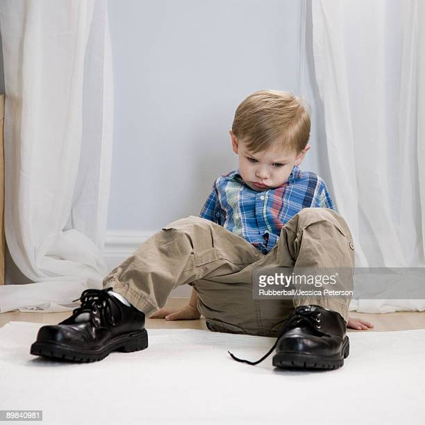 little boy wearing a man's shoes