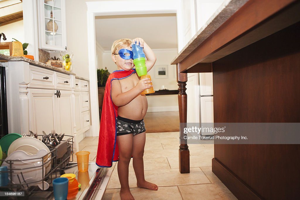 Little boy wearing a mask and cape in kitchen : Stock Photo