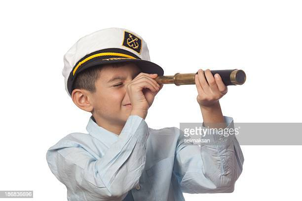 Little boy wearing captain hat looking through spy glass