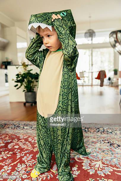 Little boy wearing dinosaur costume at home