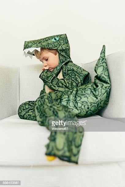 Little boy wearing dinosaur costume sitting on the couch