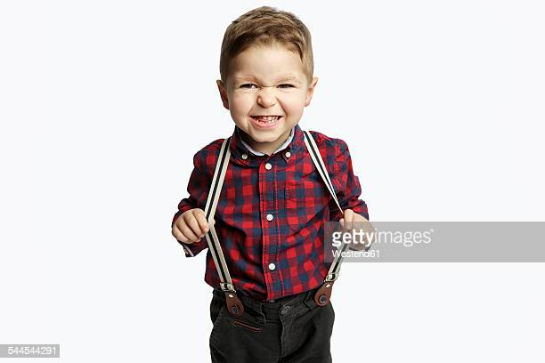 Little boy wearing suspenders pouting mouth