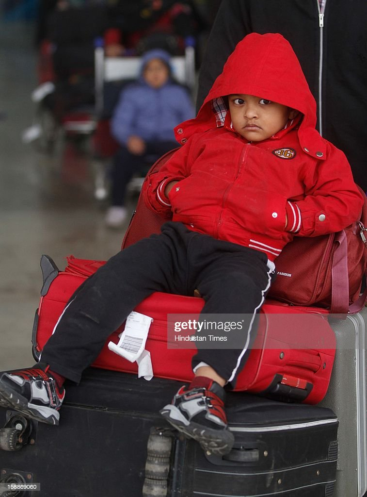 A little boy wearing warm clothes waiting at IGI Airport, as temperature dips below 6 degree Celsius on January 2, 2013 in New Delhi, India. There was no respite from cold and dense fog in North India as mercury dipped two degrees below normal to stay at 4.8 degree Celsius.