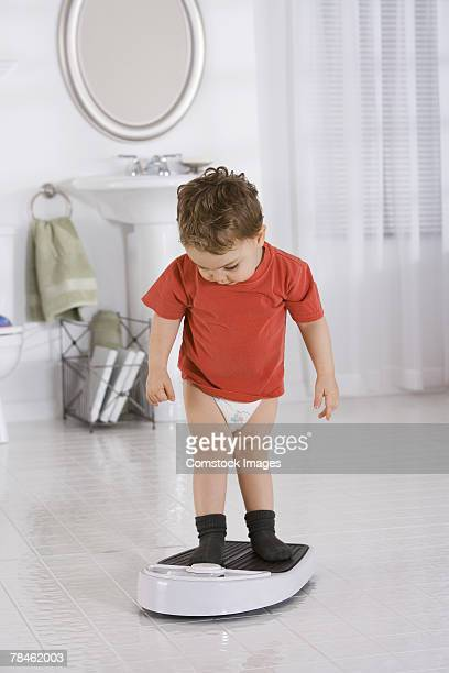 Little boy weighing himself