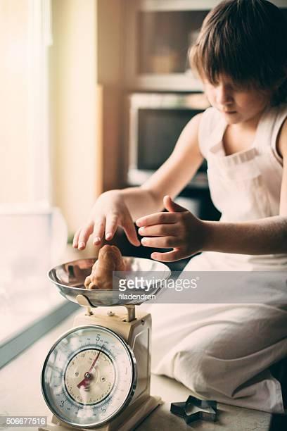 Petit garçon pèse cookies sur Balance de cuisine