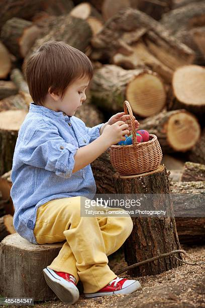 Little boy with a basket, full of colored eggs