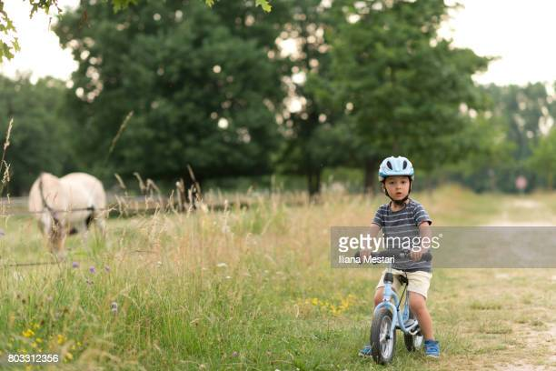 A little boy with a bicycle staring at a horse